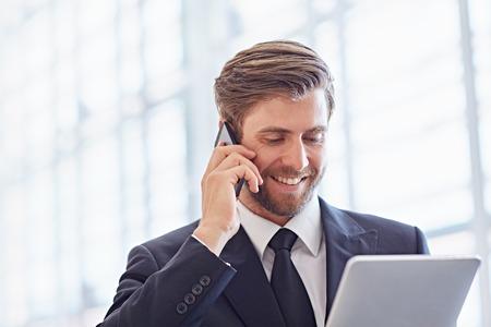 Close-up van een corporate executive glimlachen terwijl hij op zijn telefoon en kijken naar een digitale tablet