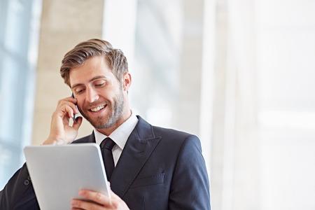 Bedrijfsleider glimlachen terwijl hij op zijn telefoon praat en naar een digitale tablet kijkt Stockfoto