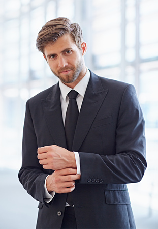 young man portrait: Portrait of a stylish corporate executive smiling confidently at the camera Stock Photo