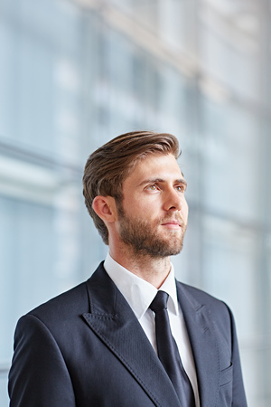 confidently: Portrait of a corporate executive looking up thoughtfully and confidently