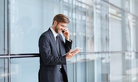 Corporate executive glimlachen terwijl praten op zijn telefoon en kijken naar een digitale tablet