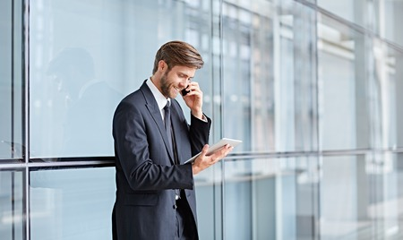 Corporate executive smiling while talking on his phone and looking at a digital tablet Zdjęcie Seryjne