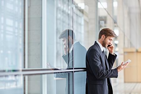 彼の携帯電話で話しながらデジタル タブレットを見て笑みを浮かべて企業経営者