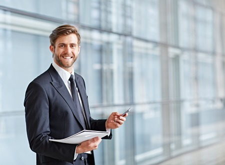 Corporate executive lachend naar de camera terwijl zijn telefoon en een nota