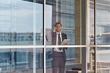 looking out: A businessman looking out the window while holding a tablet Stock Photo