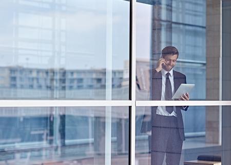 люди: Вид через окно корпоративной исполнительной говорить по телефону и, глядя на цифровой планшет