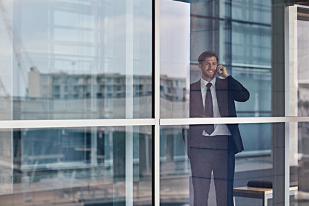 looking out: A happy businessman looking out the window while talking on his cellphone