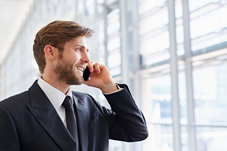 Closeup of a corporate executive looking away confidently while talking on his mobile phone