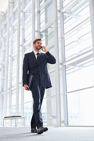 그의 휴대 전화에서 말하는 동안 걷는 기업 경영진의 낮은 각도 샷