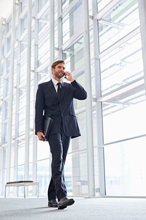 low angle: Low angle shot of a corporate executive walking while talking on his mobile phone Stock Photo