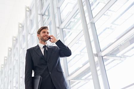 Lage hoek shot van een corporate executive lopen langs een moderne corridor te praten op zijn mobiele telefoon