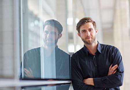 Retrato de un ejecutivo hermoso que mira positivamente a la cámara en un entorno moderno