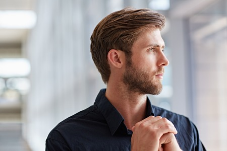 Handsome young man in a formal shirt looking seriously out into the distance photo