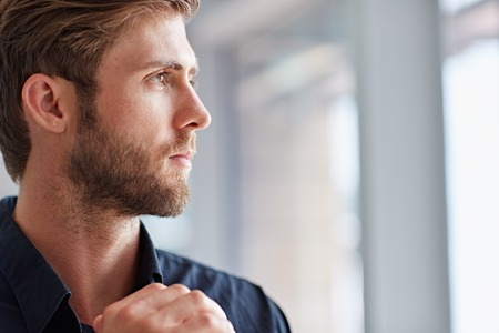 Closeup of a handsome bearded man looking away pensively photo