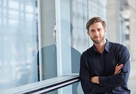 Portrait d'un beau exécutif regarder positivement à la caméra dans un cadre moderne