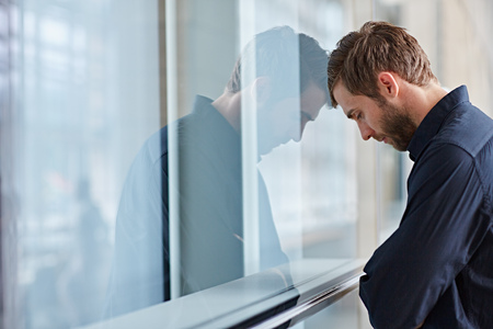 depressed: Young businessman looking depressed leaning his head against a window Stock Photo