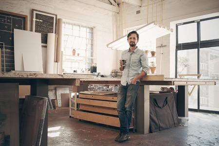 Retrato de cuerpo entero de un diseñador de sexo masculino joven que se coloca cómodamente en su taller con luz natural, sosteniendo su taza de café y sonriendo a la cámara