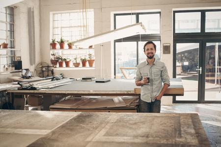 Knappe entrpreneur ambachtsman zich vol vertrouwen in zijn werkplaats studio lachend naar de camera met zijn kopje koffie in de hand