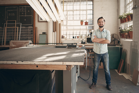 Full length portrait of a young male designer confidently standing with his arms crossed in his workshop and smiling at the camera Фото со стока