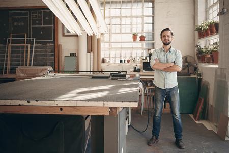 Pleine longueur portrait d'une jeune créatrice mâle confiance debout, les bras croisés dans son atelier et souriant à la caméra