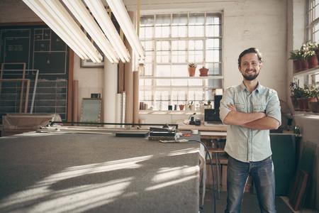 företag: Porträtt av en snygg manlig designer som står i hans verkstad studio med armarna i kors och ler med tillförsikt mot kameran
