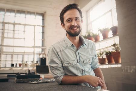 Portret van een jonge mannelijke ontwerper op zijn werkbank leunend en het geven van de camera een ontspannen en vriendelijke glimlach
