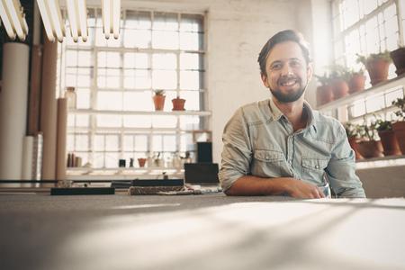 부드러운 sunflare이 창을 통해 들어오는 그의 스튜디오에서 휴식하는 동안 카메라에 미소 잘 생긴 디자이너 entrepeneur 스톡 콘텐츠