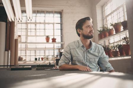 Knappe jonge mannelijke kleine ondernemer zit in zijn studio workshop positief denken terwijl weg te kijken in de verte Stockfoto