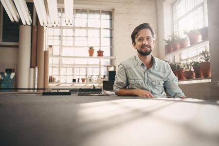 사업: 중소 기업 소유자의 초상화 그의 worskhop 스튜디오에서 부담없이 앉아 자신감과 긍정적 인보고