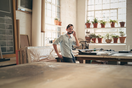 framer: Handsome craftsman standing casually in his workshop studio talking on his phone with a positive expression Stock Photo