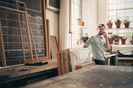 Small business owner talking on his phone while smiling and standing casually in his studio workshop Foto de archivo