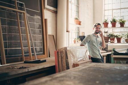 Propriétaire de petite entreprise de parler sur son téléphone tout en souriant et debout par hasard dans son atelier studio
