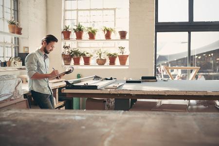 Joven dueño del negocio masculino de pie en su estudio taller comprobar figuras y social en su portapapeles en una tarde soleada Foto de archivo