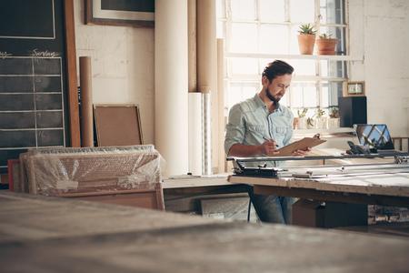 Männliche Unternehmer Handwerker Aufträge und Figuren auf einer Zwischenablage überprüft, während beiläufig in seinem Atelier Werkstatt stehen Standard-Bild - 51813673