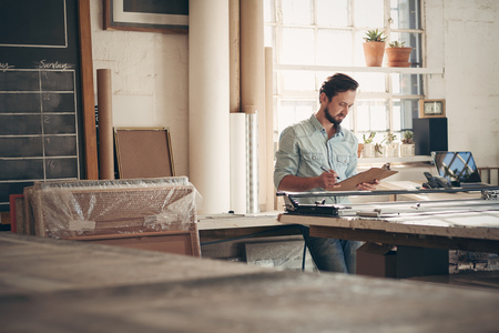 Maschio imprenditore artigiano controllando gli ordini e le cifre su un blocco per appunti in piedi casualmente nel suo laboratorio di studio