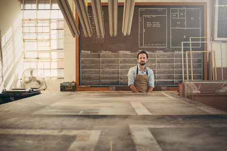 picture framing: Handsome carpeter businessman sitting in his workshop in front of a daily schedule drawn on a chalk board, looking confidently at the camera
