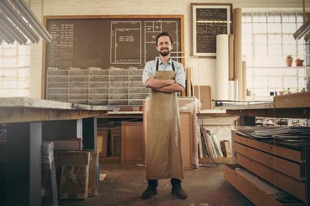 confianza: Retrato de cuerpo entero de un artesano desigern con confianza de pie con los brazos cruzados en su taller y sonriendo a la cámara