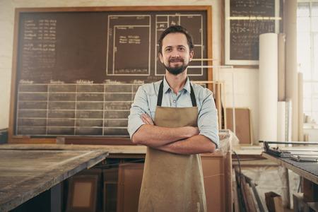 Portret van een ontwerper ambachtsman zich in zijn atelier studio met zijn armen gevouwen en lachend positief op de camera Stockfoto
