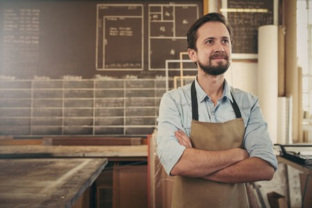 picture framing: Cratsman looking away in a thoughtful manner with his arms folded while standing in his carpentry workshop and smiling to himself Stock Photo
