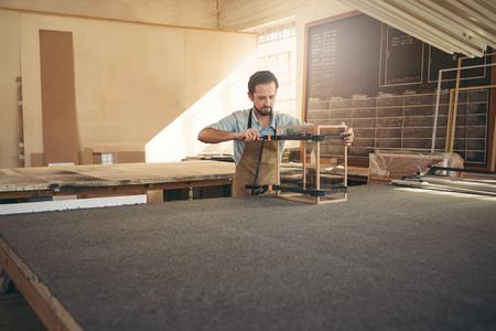carpintero: el taller de carpintero con un artesano construcción de una vitrina de madera y vidrio Foto de archivo