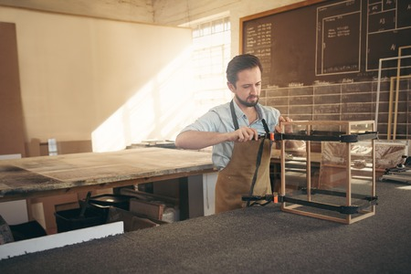 framer: Craftsman carefully manufacturing a glass and wood display case in his workshop Stock Photo