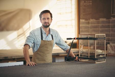 彼は注意を払って作っている木材、ガラスの陳列ケースと一緒に彼のワーク ショップに誇らしげに立っている間カメラに笑顔の職人 写真素材