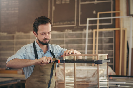 display case: Focused capenter carefully making a wood and glass display case in his workshop with the skill of his trade