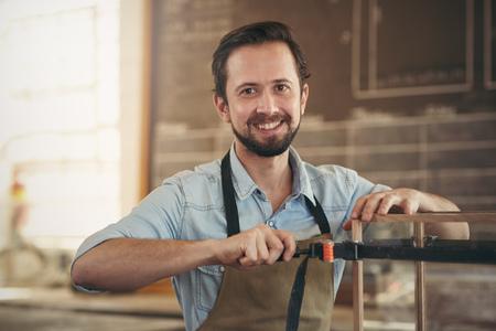 Portret van een ambachtsman met behulp van een tool om een houtbewerking project produceren in zijn atelier Stockfoto