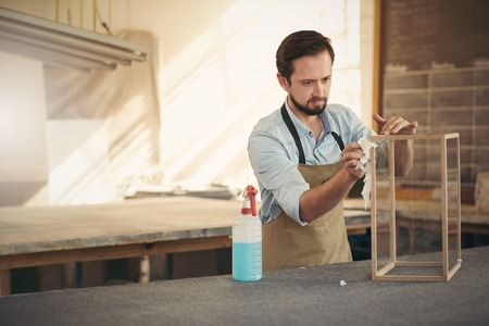 framer: Craftsman designer concentrating while applying the finishing touches to a project in his woodwork workshop