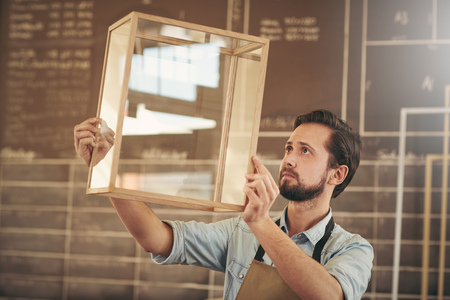 entrepreneurial: Designer looking carefully at a new product made from glass and wood in preparation for entrepreneurial marketing