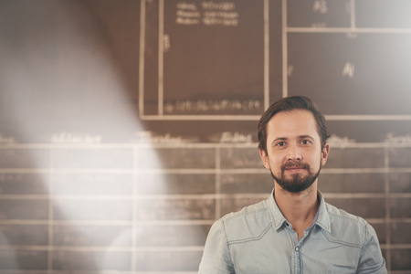 picture framing: Handsome designer businessman standing in his workshop in front of a chalk board, looking confidently at the camera