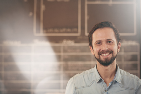 framer: Head and shoulders portrait of a handsome craftsman and designer in his studio smiling at the camera Stock Photo