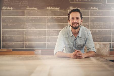 personas mirando: diseñador masculino joven hermoso en su estudio apoyado cómodamente en su banco de trabajo en sus brazos y sonriendo con una sonrisa positiva a la cámara