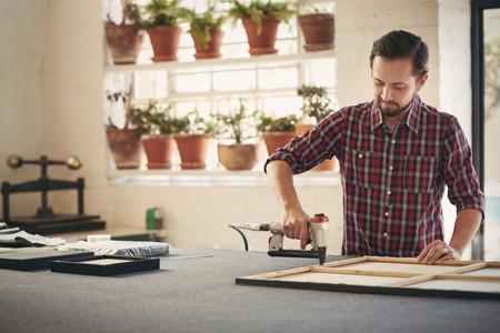 Geschoolde lijstenmaker drukke framing een kunstwerk en met behulp van een gespecialiseerde werk hulpmiddel om de taak te voltooien in zijn atelier